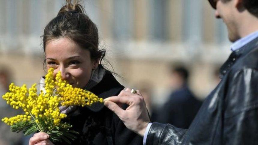 Mulher segura flores ganhadas no dia da mulher
