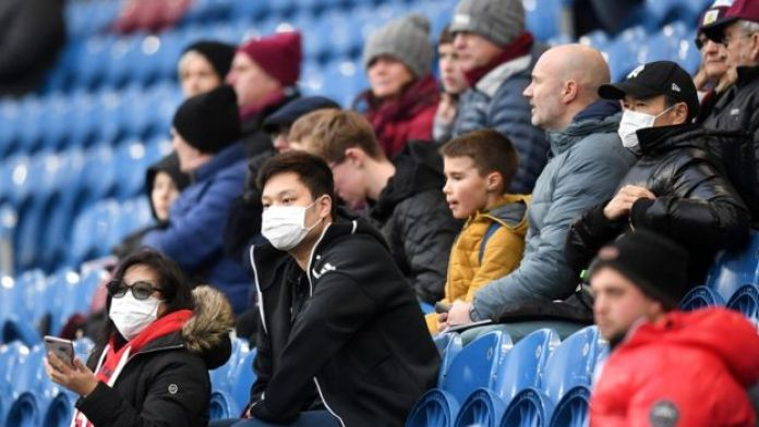 Fans wear disposable face masks prior to the Premier League match between Burnley and Tottenham at Turf Moor