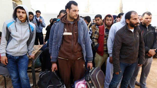 Migrants wait with their luggage in Libya