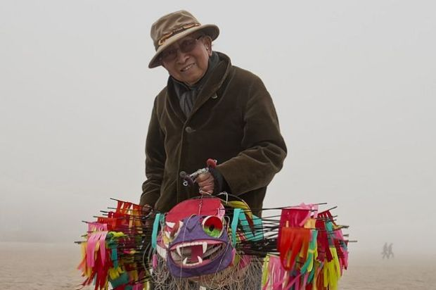 A photograph shows Tyrus Wong holding one of his intricately made bamboo kites on the beach