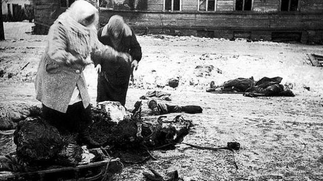 Dos figuras femeninas recogen los restos de un caballo muerto para comer, durante el asedio de Leningrado.