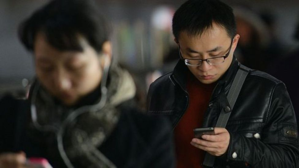 صينيان يستخدمان تطبيقات الإنترنت عبر الهاتف