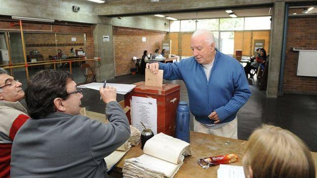Hombre de cabello blanco insertando un voto en un ánfora.