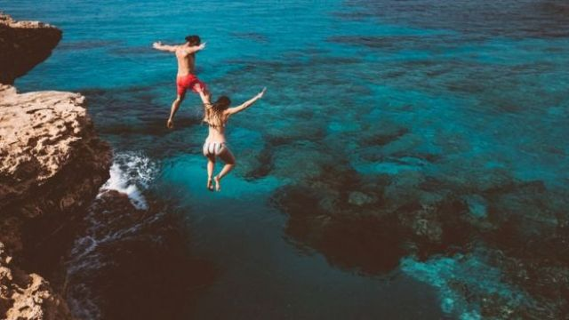 A couple jumping into turquoise blue waters