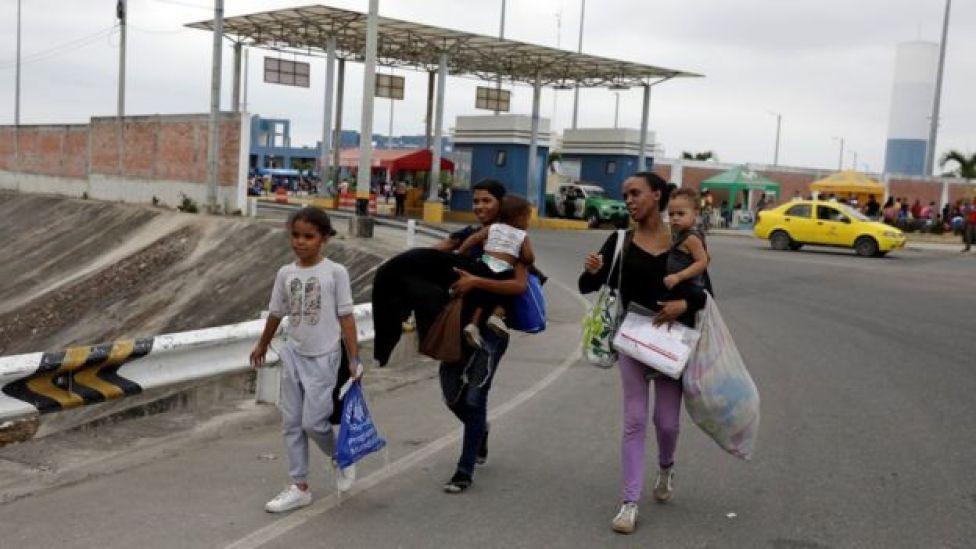 Venezuelans walk together with their children after entering Peru