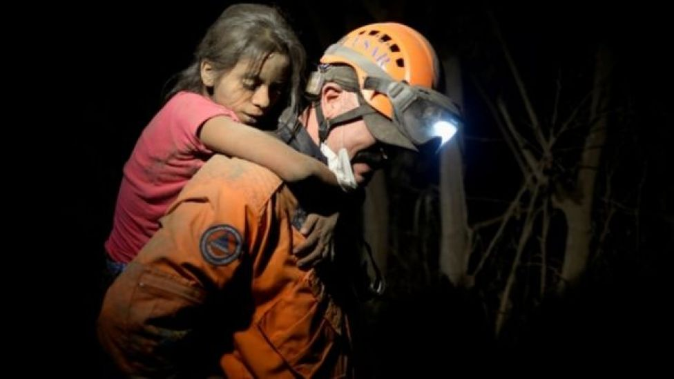 A rescue worker carries a child covered with ash after Fuego volcano erupted in El Rodeo, Guatemala, 3 June 2018