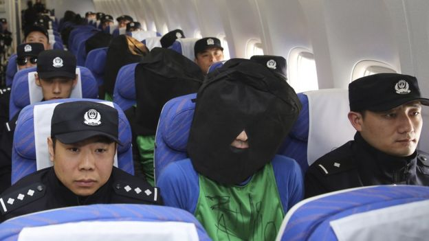 In this photo released by Xinhua News Agency, Chinese suspects involved in wire fraud, center, sit in a plane as they arrive at the Beijing Capital International Airport in Beijing on Wednesday, 13 April 2016