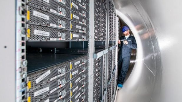 Un hombre en los estrechos confines del tubo abierto trabaja en una computadora en un estante de máquinas de idéntico tamaño