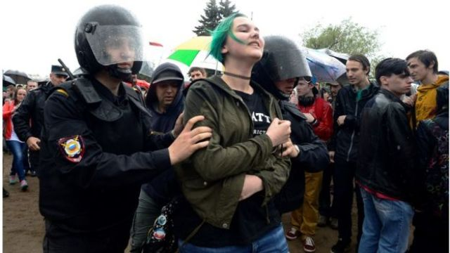 Russian police officers detain a young woman participating in an unauthorised opposition rally in centre of Saint Petersburg on June 12, 2017