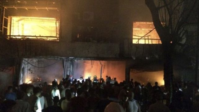 Iraqi fire fighters and civilians gather at the site of a car bomb at a commercial area in the Karrada neighbourhood of Baghdad (03 July 2016)
