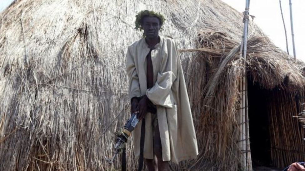 A man holding a rifle stands in front of a hut.