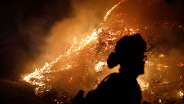 Firefighters stand watch as the Kincade Fire burns in Santa Rosa