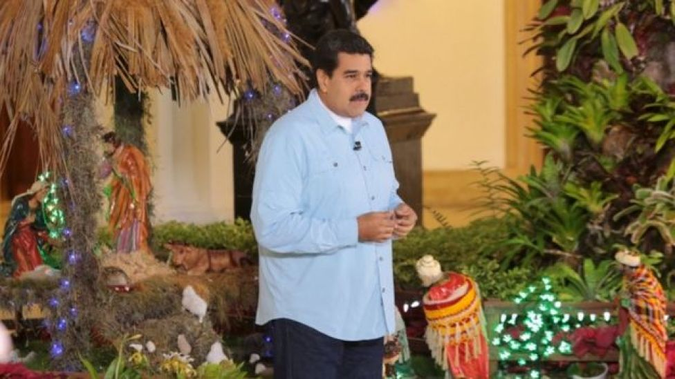Venezuela's President Nicolas Maduro speaks in front of a nativity scene during his weekly broadcast