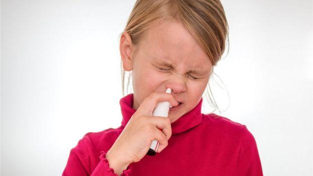 Girl using a nasal spray