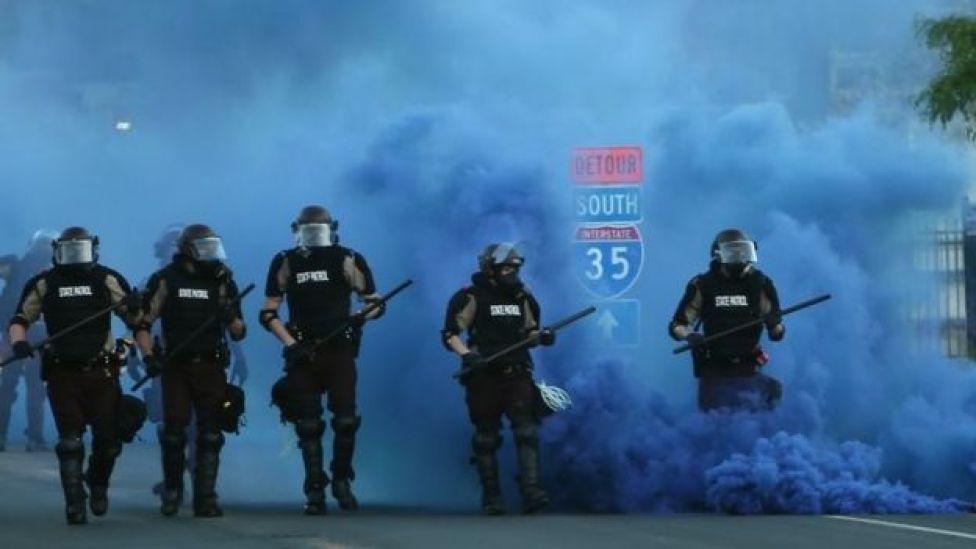 Policías avanzan en medio de una nube de gas