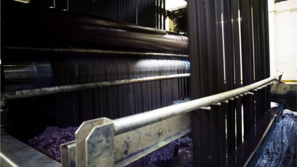 Denim threads are dipped into indigo baths in a rope dying machine at a jeans factory