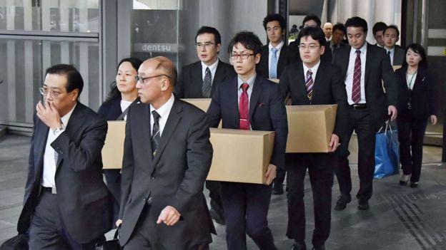 Funcionarios del Ministerio de Trabajo saliendo de la sede de Dentsu con cajas de cartón