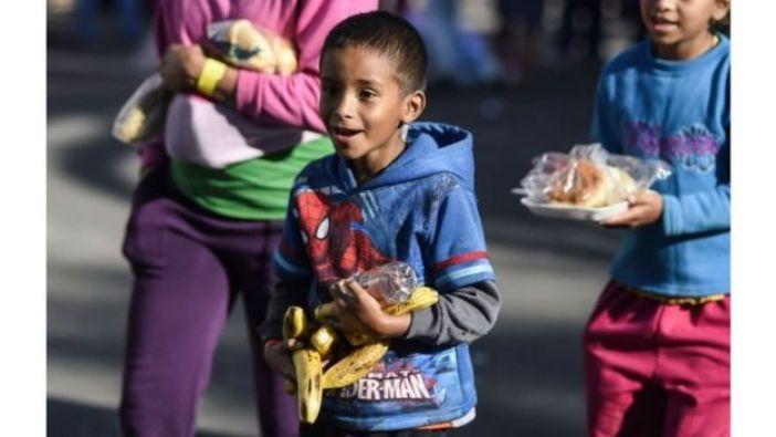 Niños migrantes con comida.