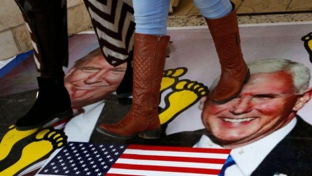 Palestinos caminando sobre un póster de Donald Trump y Mike Pence en diciembre.