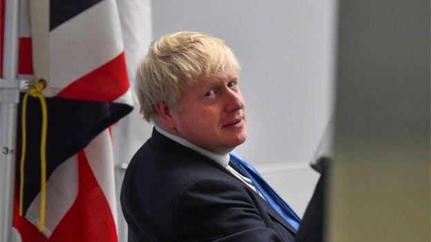 Boris Johnson next to a British flag