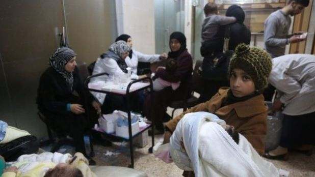 A girl holds her baby sister as they wait for measles vaccinations at a medical centre in the eastern Ghouta area on the outskirts of Damascus (18 March 2017)