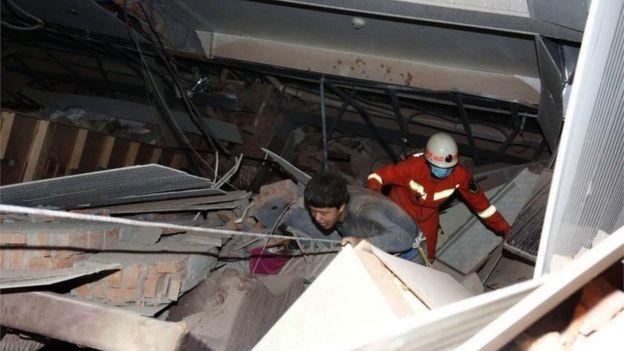 2020年3月7日、中国南東部の福建省の泉州市にある倒壊した5階建てのホテルの瓦の外を歩いて負傷した男性を救助者が追う