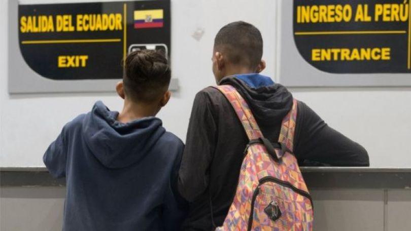 Imagem mostra dois jovens de costas, na fronteira do Equador com o Peru