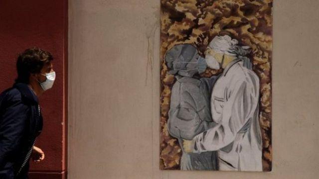 Homem passa diante de quadro em que pessoas se beijam de máscara