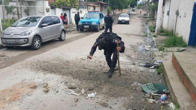Policial destruindo barricada