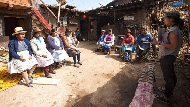Mujer del proyecto Quipu conversando con otras mujeres