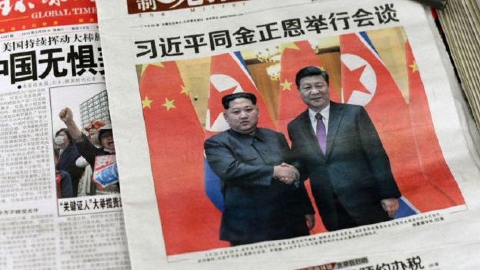 Images of Xi Jinping with Kim Jong Un, are displayed at a newspaper stand in Beijing on March 28, 2018