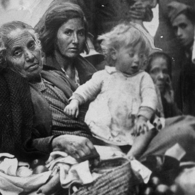 Una anciana, junto a su hija y a su nieta, refugiadas todas de la guerra civil española, llegan a Valencia cargando sus pertenencias en 1937.