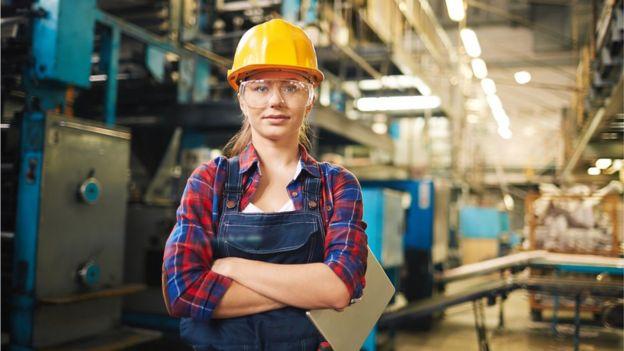 Mujer ingeniera con un casco en una fábrica