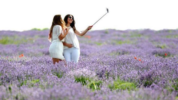 Dos jóvenes tomándose un selfie en un campo de lavanda