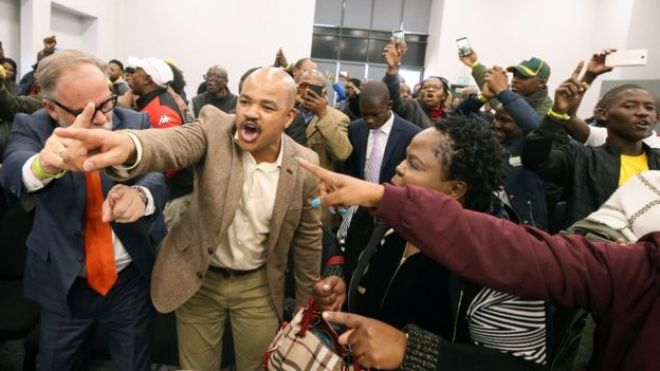 Supporters of former South African President Jacob Zuma sing and dance during a break in proceedings