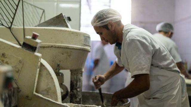 Homem de touca e jaleco trabalha com maquinário