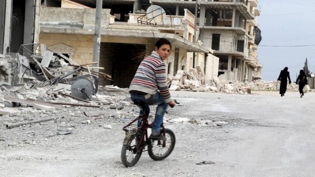 A boy rides a bicycle in Kafr Hamra, northern Aleppo province (27 February 2016)