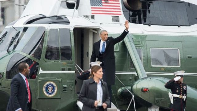 Former President Barack Obama waves as he departs the inauguration in Washington.