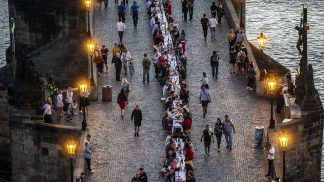 Les gens sont assis à une longue table sur le pont Charles
