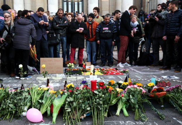 People leave tributes at the Place de la Bourse following attacks in Brussels