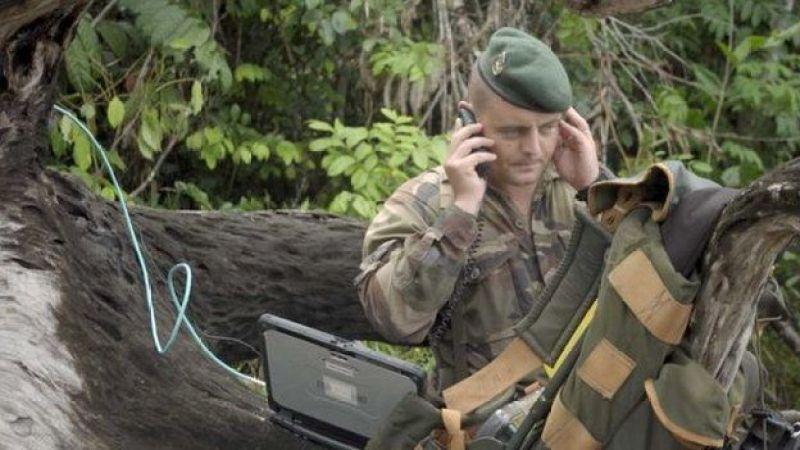 Capitão Vianney, fardado, fala no celular no meio da floresta