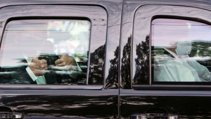 President Donald Trump gives two thumbs up to supporters as he rides in the presidential SUV with two Secret Service agents wearing medical protective masks, goggles and protective gowns