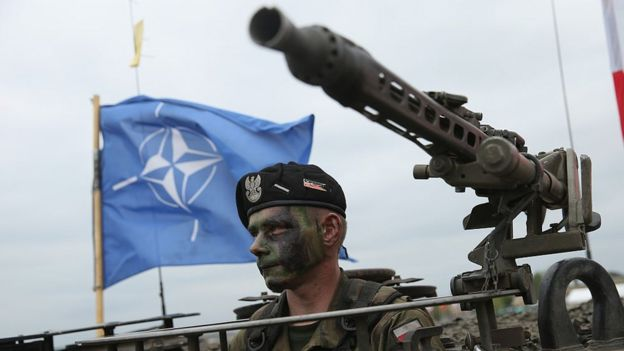 soldier of the Polish Army sits in a tank as a NATO flag flies behind during the NATO Noble Jump military exercises