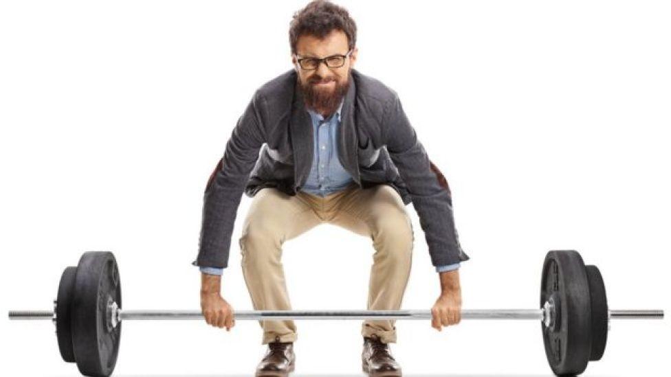 Hombre con ropa casual levantando una barra de peso libre.  Qué tipo de deporte es mejor para estar sano según tu edad  105556392 pesas