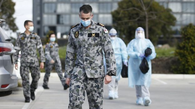 A soldier wearing a mask walks out of a nursing home with other medical responders