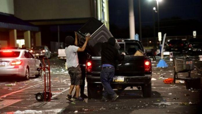 Des gens placent des marchandises d'une quincaillerie dans un camion lors d'une opération de grande envergure à Philadelphie, en Pennsylvanie, le 31 mai 2020