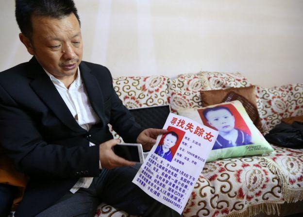 الأب يحمل صورة ابنته