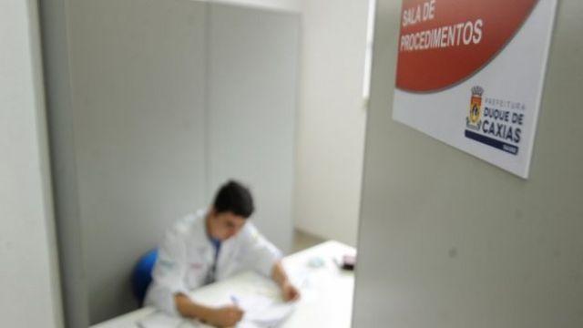 Médico aparece escrevendo dentro de consultório