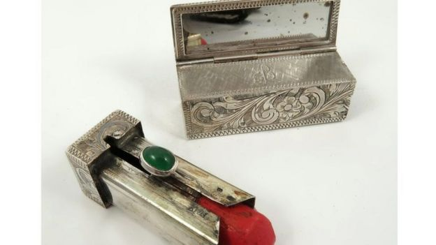 A silver lipstick case and red lipstick