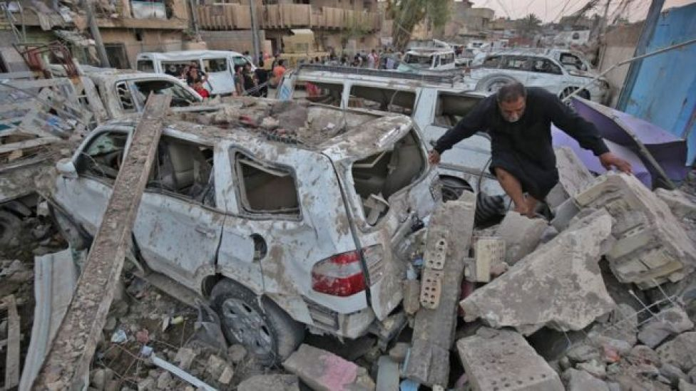 Iraqis inspect the aftermath of explosions that destroyed a mosque in Baghdad's Sadr City district (7 June 2018)
